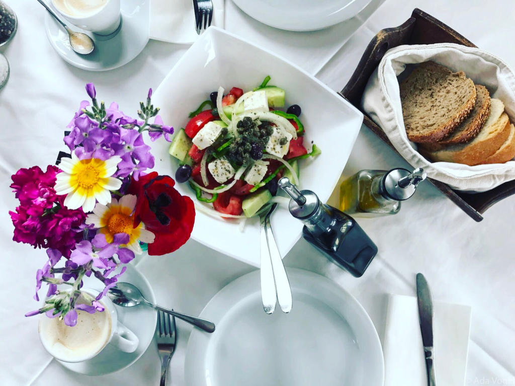 Greek salad in Satorini with oils and beautiful bread. Espresso's and colourful flowers on a white linen cloth