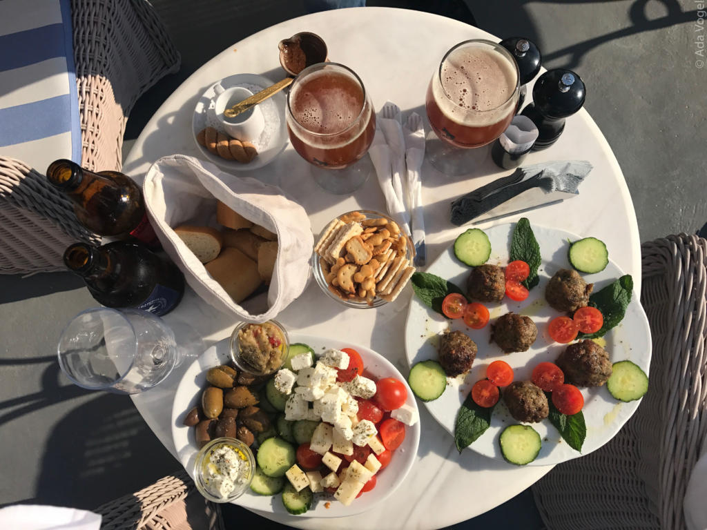 Greek plate of feta cheese, tomatoes and cucumber with meatballs, bread, crackers and beer