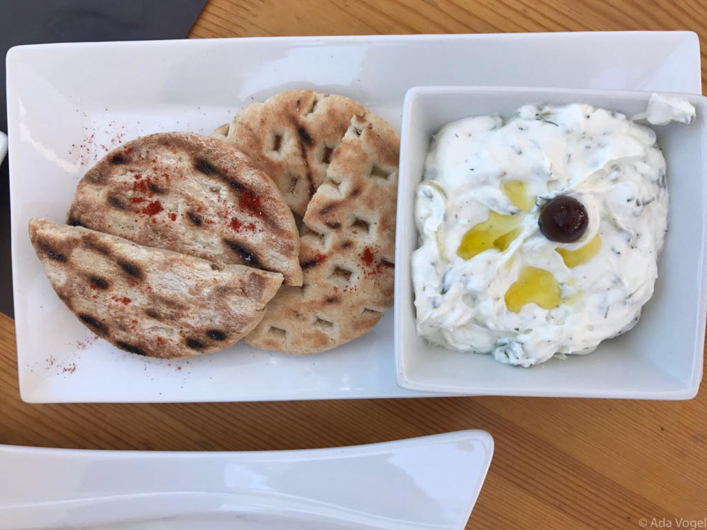 Homemade Greek Tzatziki with olive oil and an olive for decoration. Pitta bread dusted with paprika