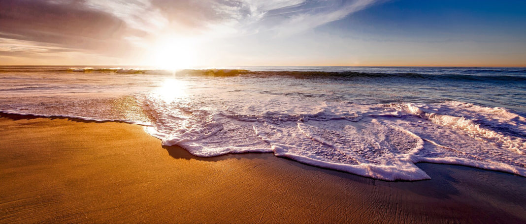 waves crashing on a beach as the sun sets on the horizon